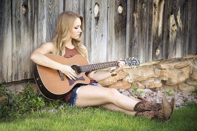 壁にもたれ掛かってギターを弾く女性